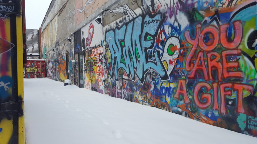 An alleyway with graffiti. Covered in snow